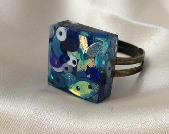 Blue sequin ring set in resin.