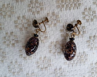 The dangling vintage brown black earrings of glass beads and metal parts.