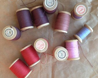 Spools of threads set. Vintage organic cotton 12 threads spools in pink-purple colors. Not used and used wooden spools.