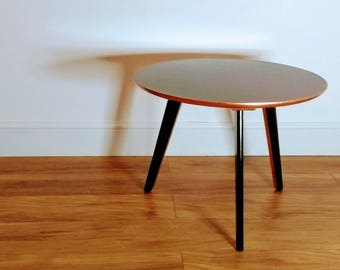 1960's Round coffee table with mahogany Formica top and black Ebonised base with copper leaf detail.