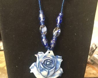 Blue  beaded  necklace with shell with cut rose pendant