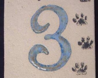 Modern and original door number, number 3, beige background, black cat paw