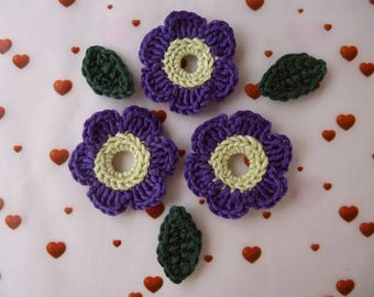 3 purple and light green flowers and 3 green leaves crochet
