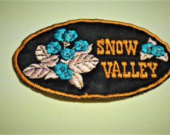 Snow valley applique, embroidered blue and pink flowers amid black 9 cm orange outline