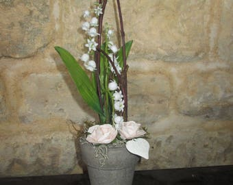 Artificial flower arrangement with Lily of the Valley in a clay pot.