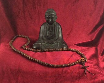 Buddhist-style long wood bead mala with carved wood skull and decorative knot