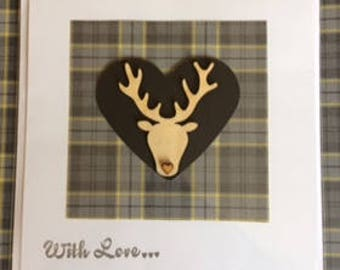 Wooden stag's head on black heart and grey tartan background.