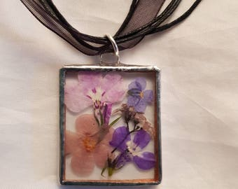 Pressed flowers in glass pendant.