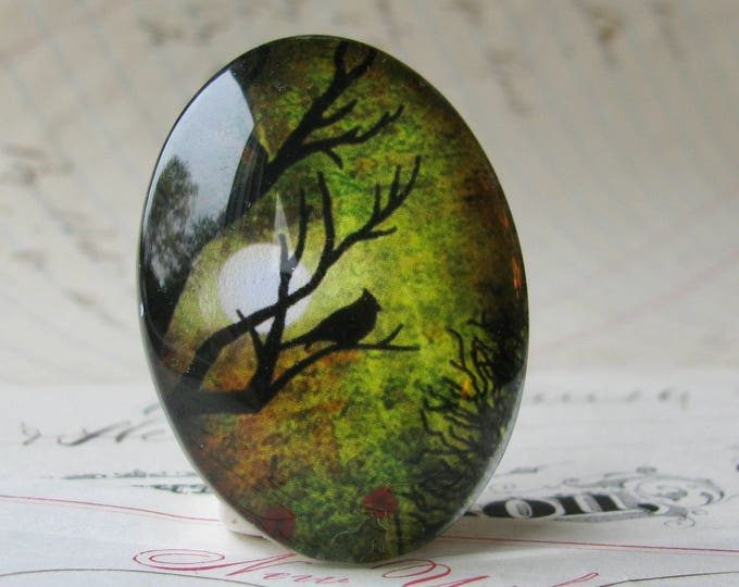Bird in a tree silhouette against a full moon, 40x30mm handmade glass oval cabochon, olive green sky, sunset, from or Mystic Moon collection