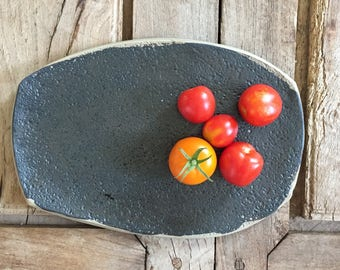 Satin black serving tray with textured surface and raw clay edge