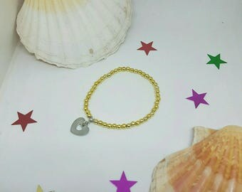 Gold beaded bracelet and a heart charm