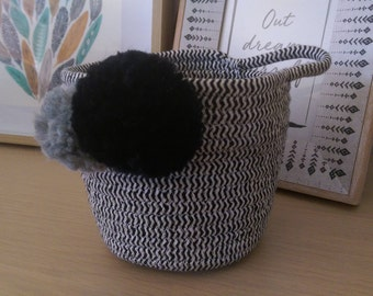 Cute black and white basket with handle, adorned with woollen pom poms