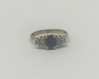 9ct Gold Oval Sapphire Ring Set In A Cluster Of Diamonds