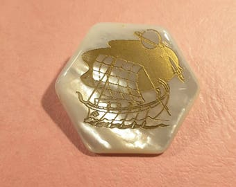 Large mother of pearl button depicting Viking longboat at sea.