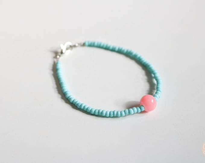 Skinny Pastel Blue Bracelet with Feature Pink Bead.