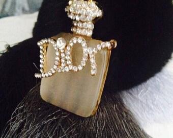 Black & white furry pom pom keychain with perfume bottle logo