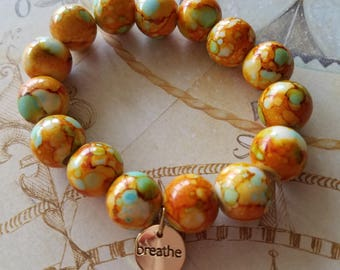 """Hand Made stretchy acrylic bracelet in burnt orange, with """"breath""""gold tone charm"""