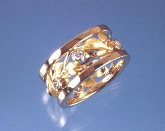 Leaves and diamonds wrap all around this custom wedding band in 18k yellow and white gold