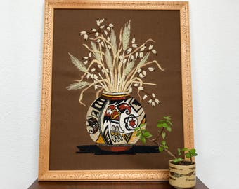 Vintage crewel art featuring a Native American pot / yarn painting in carved wood frame