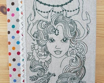 A5 Hard backed Note book covered with a machine embroidered design.