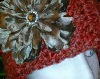 Large Winter hat burnt orange with large  taupe flower clip that has a shimmer to it and a pretty faux gem in the middle. Removable flower