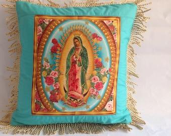 Virgin of guadalupe handmade fabric with gold tassel fringing, cushion, pillow. Turquoise. Robert kaufaman fabric