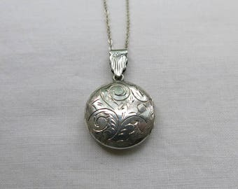 Vintage round silver locket prettily engraved back and front