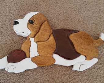 Adorable beagle dog wall hanging. Dog is white, light and dark brown. It's ball is red