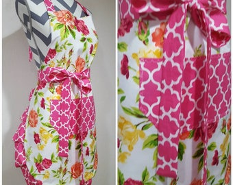 Adult apron. Woman's apron. Bright orange, yellow and pink floral on main.  Pink pocket, ties and frills.