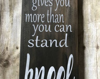 When life gives you more than you can stand kneel. Wooden wall sign.