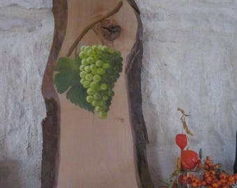 Green grapes on painting on wood with bark chestnut