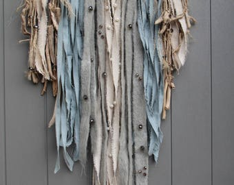Wall hanging with driftwood, fabrics, boiled wool and beads in soft shades of blue/beige
