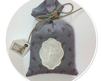 "BAG OF LAVENDER EMBROIDERED WITH A MONOGRAM LETTER ""V"" IN LOCKET"