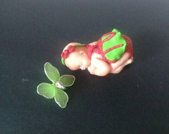 polymer clay with a green and pink dress baby