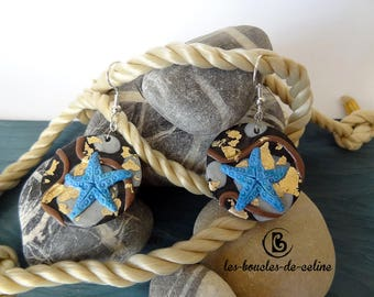 Earrings: Blue starfish on a black and gold background