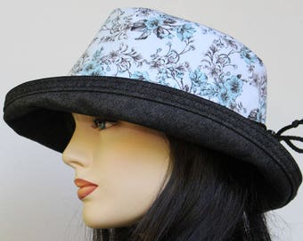 Sunblocker UV summer sun hat with large wide brim featuring gray blue and black delicate floral print and adjustable fit