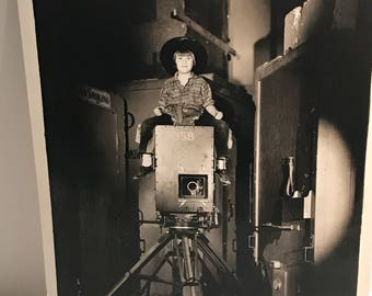 Old photograph of little girl sitting on too of a movie camera