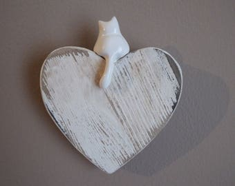 ceramic cat on wooden heart