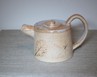 Small stoneware teapot with imprints of leaves and plants
