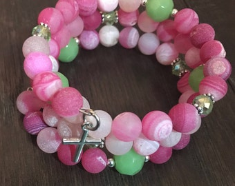 pink and green memory wire bracelet with cross charm