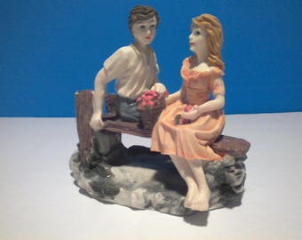 Boy and Girl Courting while sitting on a bench.