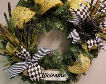 "24"" evergreen wreath with yellow mesh, black and white ribbon and a metal welcome sign"