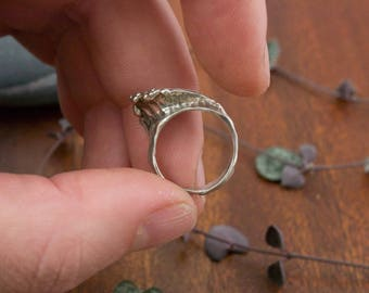Tiny silver breaking wave ring - a rolling wave breaking on a shore, captured in sparkling sterling silver split ring