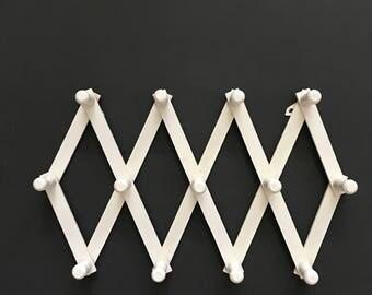 white wood accordion wood peg wall hanging rack // hat display storage // organizer