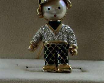 Figural man brooch with rhinestone shirt and basebal hat enamel pants may be signed cutie for sure