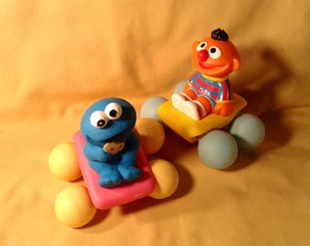 Set of 2 Baby, Toddler Squishy Rubber Car Toys - Baby Cookie Monster in Pink Car with Yellow Wheels & Ernie in Yellow Car with Blue Wheels