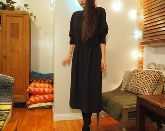 black mid length party dress with dolman sleeves and button detail