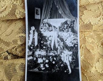 Antique post mortem baby child in an open casket with floral arrangements