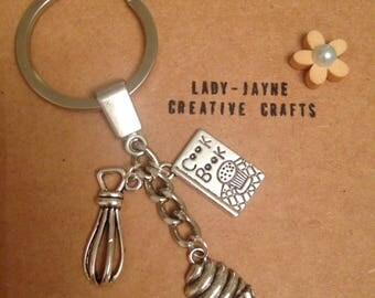 A Great British Bake Off keyring. A brilliant unique keyring for someone cooking mad. Keyring contains cupcake, recipe book & whisk charms
