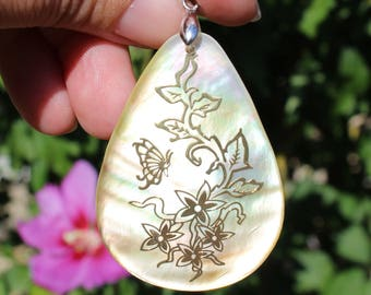 1 PEARL SHELL PENDANT PRINTED IN GOLD WITH ATTACHED PENDANT SILVER. 40 X 55 X 2 MM.